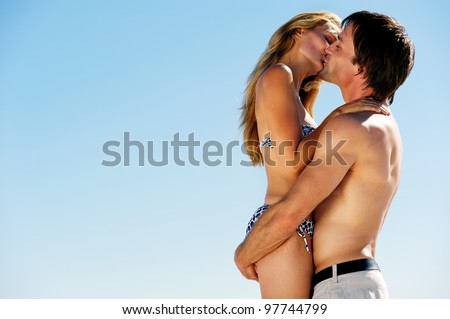 kissing summer beach couple on vacation in a tropical island scene - stock photo