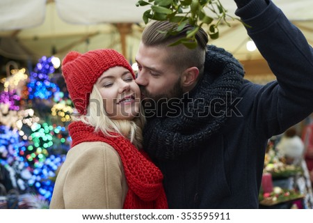 Kissing under the mistletoe is a tradition - stock photo