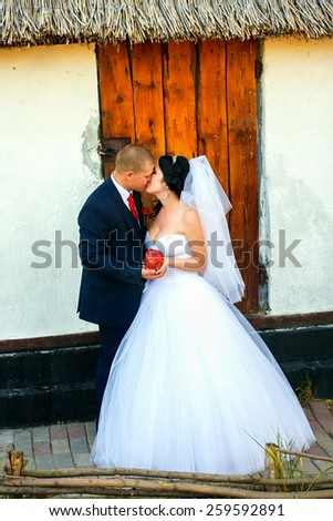 Kissing wedding couple in spring nature close-up portrait