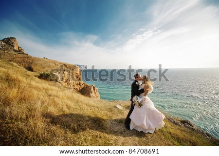 Kissing wedding couple staying over beautiful landscape - stock photo
