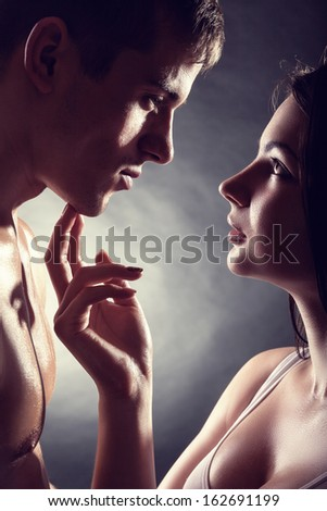 Kissing young couple on a dark background - stock photo