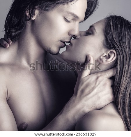 Kissing young couple on a gray background - stock photo