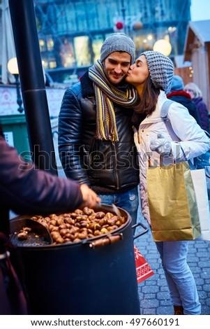 Kissing young couple walking on the street at wintertime, buying roasted chestnuts.