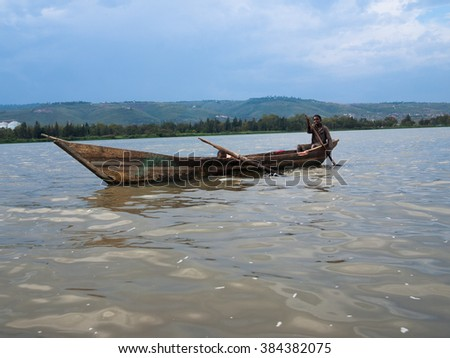 KISUMU, KENYA - AUGUST 08, 2013. Two young poor African boys sailing in a wooden boat on Lake Victoria on the background of the hills with trees and cloudy sky. One boy holding a paddle and smiling - stock photo
