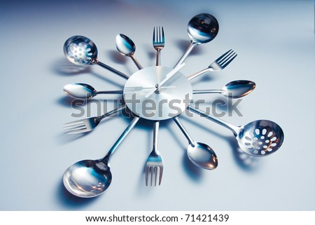 Kitchen abstract clock witch spoon and fork. Dramatic light used - stock photo