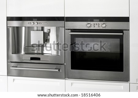 Kitchen appliances coffee machine and electric oven - stock photo