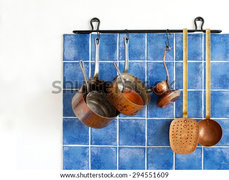 Kitchen appliances. Hanging retro design copper kitchenware set. Pots, stewpots, saucepans, coffee maker, kitchen spoon, skimmer hanging on. Blue tiles wall background. - stock photo