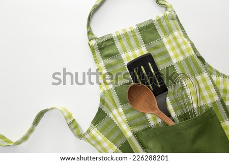Kitchen apron and utensils - stock photo