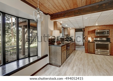 Kitchen area with red brick wall and built in appliances. Empty window seat overlooking back yard. Large wooden house interior.  Northwest, USA