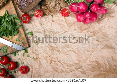 Kitchen background with baking paper, tomatoes, radish and parsley