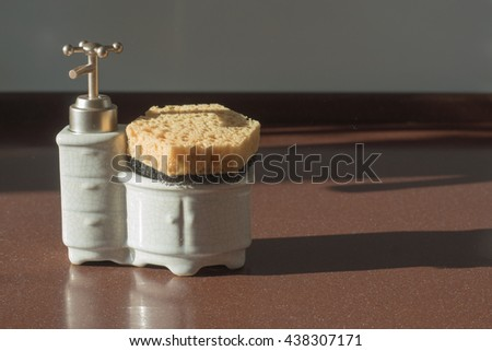 Kitchen ceramic white dispenser for soup with sponge holder for dish cleaning in a shape of little washbasin on a background of brown table - stock photo