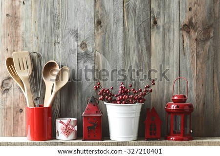 Kitchen cooking utensils in ceramic storage pot and Christmas decor on a shelf on a rustic wooden wall - stock photo