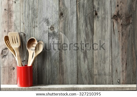 Kitchen cooking utensils in ceramic storage pot on a shelf on a rustic wooden wall, space for text - stock photo
