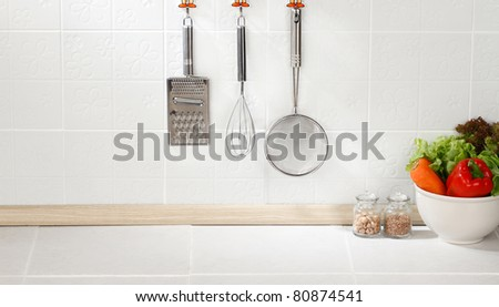 Kitchen cooking utensils on hook against tile wall - stock photo
