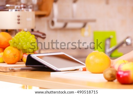 Kitchen counter with many fruits and tablet device. Healthy eating, cooking, vegetarian food, dieting and technology concept.