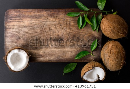 Kitchen cutting board and coconut with green leaves isolated on a black background