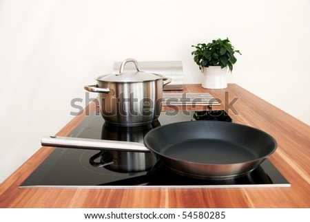 kitchen detail with induction electric hob, pan and pot - stock photo