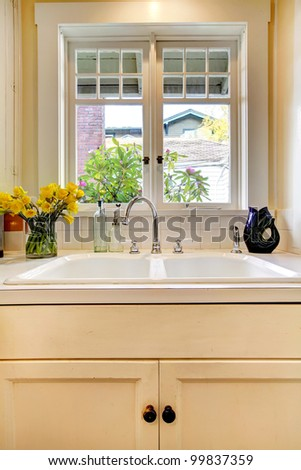 Kitchen double sink and white cabinet with window. - stock photo