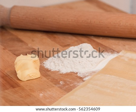 Kitchen dough preparation scenery with white flour, eggs, piece of butter, rolling pin and a copper backing tray on a wooden surface.