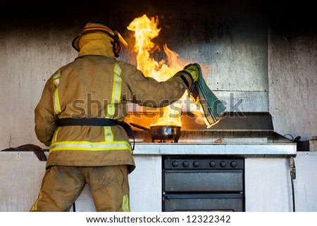Kitchen fire being put out by a fireman