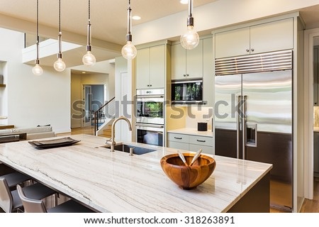 Kitchen in House: Kitchen Interior with Island, Sink, Cabinets, Stainless Steel Refrigerator, Pendant Lights, and Hardwood Floors in New Luxury Home - stock photo