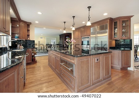 Kitchen in luxury home with black marble counter tops - stock photo