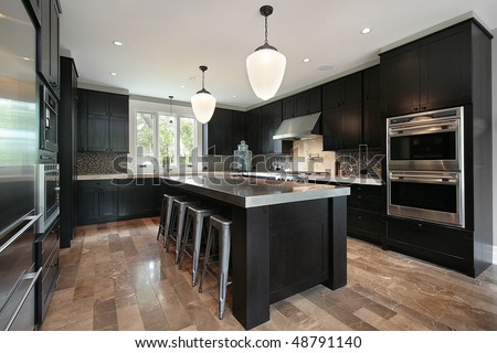 Kitchen in luxury home with dark wood cabinetry - stock photo