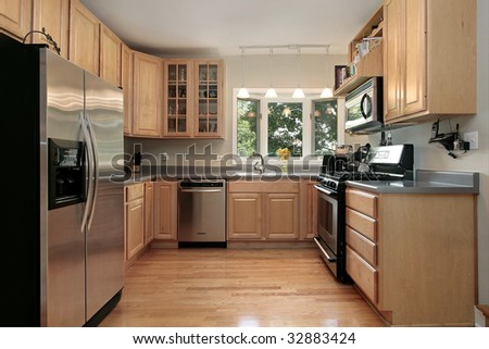 Kitchen in luxury home with oak cabinetry - stock photo