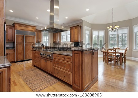Kitchen in luxury home with wood and granite island - stock photo
