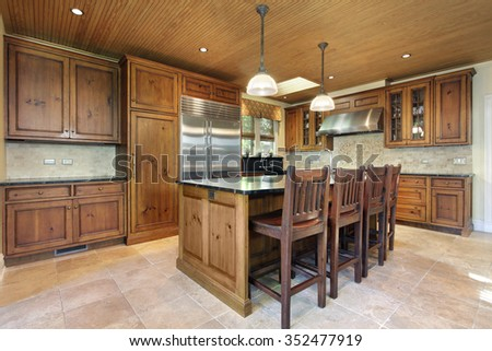 Kitchen in luxury home with wood cabinetry - stock photo