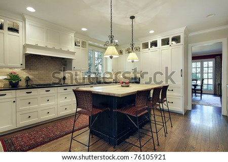 Kitchen in luxury home with wood island - stock photo