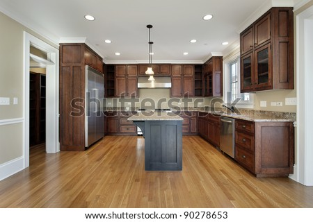 Kitchen in new construction home with island - stock photo