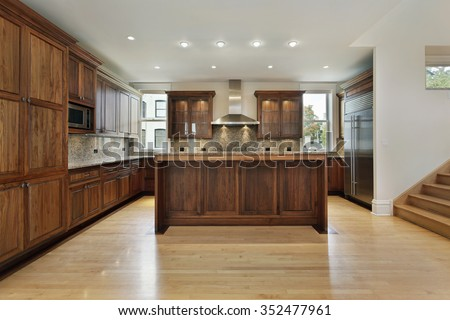Kitchen in new construction home with wood cabinets - stock photo