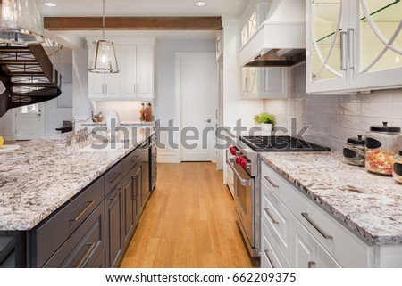 Kitchen in New Luxury Home. Hardwood floors separate elegant kitchen island and counter with oven, range, and hood. Includes eye catching glass fronted cabinets