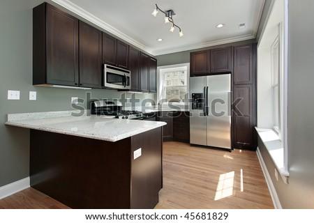 Kitchen in remodeled condominium unit mahogany cabinetry - stock photo