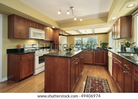 Kitchen in remodeled home with black granite counters - stock photo