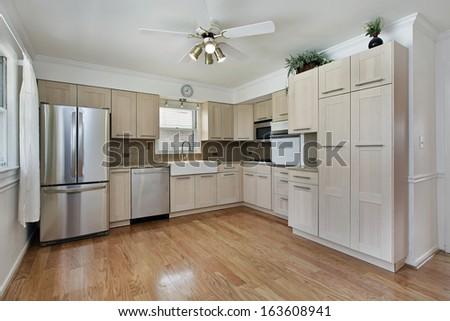 Kitchen in remodeled home with tan cabinetry - stock photo