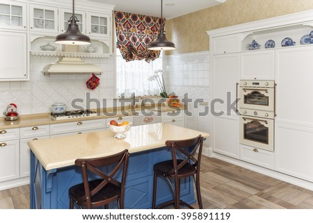 Kitchen in the magnificent house with a blue table the island - stock photo