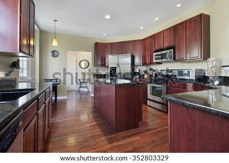 Kitchen in upscale home with cherry wood cabinetry - stock photo