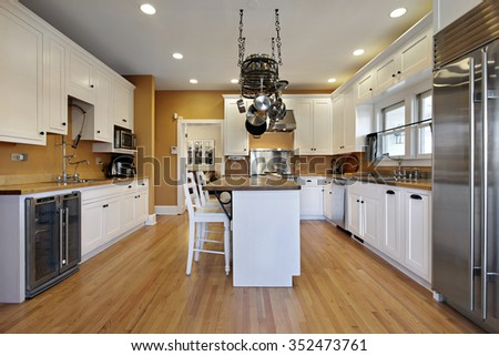 Kitchen in upscale home with gold colored walls - stock photo