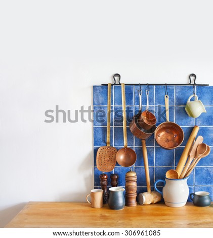 Kitchen interior, accessories. Hanging copper kitchenware set. Spoon, skimmer, colander. Blue tiles ceramic background. Wooden spoons, pitchers and cup on the table. copy space. - stock photo