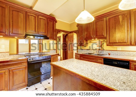 Kitchen interior design with island, granite counter top and tile floor - stock photo