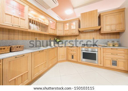 Kitchen interior designed in beige color and decorated in wood in furniture salon - stock photo
