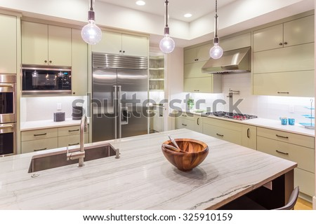 Kitchen Interior Detail with Island, Sink, Cabinets, and Hardwood Floors in New Luxury Home - stock photo