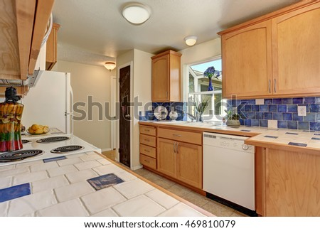 Kitchen interior. Maple cabinets with white and blue tile counter top , back splash trim and white appliances. Northwest, USA