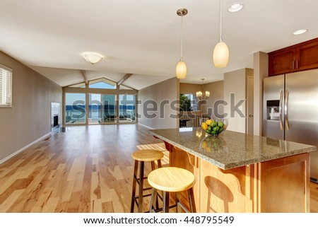 Kitchen interior with bar, stainless steel fridge, hardwood floor in luxury house. Empty spacious room with exit to the balcony.