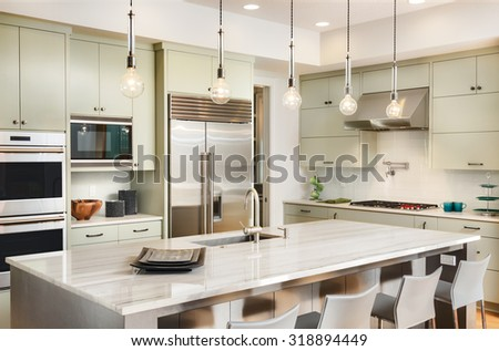 Kitchen Interior with Island, Sink, Cabinets, Stainless Steel Refrigerator, Oven, and Hardwood Floors in New Luxury Home - stock photo