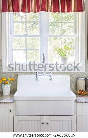 Kitchen interior with large rustic white porcelain sink and granite stone countertop under sunny window - stock photo