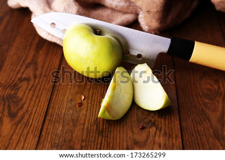 Kitchen knife and green apple,   on wooden background - stock photo