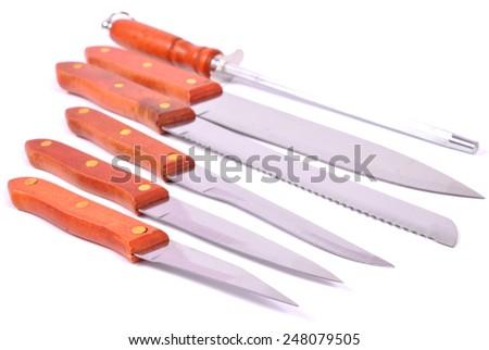 Kitchen knives and knife sharpener on white - stock photo